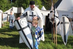 Ritter begrüßt kleinen Jungen im mittelalterlichen Zeltlager